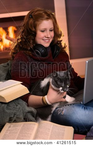 Smiling teenage girl sitting at fireplace at home learning with laptop and books. Happy brainy preoccupation.