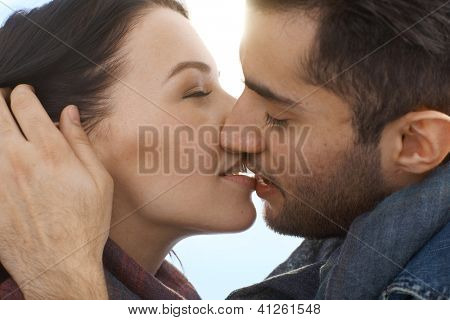 Closeup photo of young loving couple kissing.