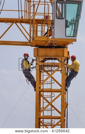 Two Men at Work on Crane Assembly, Italy