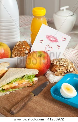 Lunchbox with a love note on the breakfast table