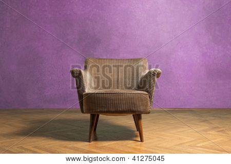 Vieja silla en la sala de grunge con pared rosa
