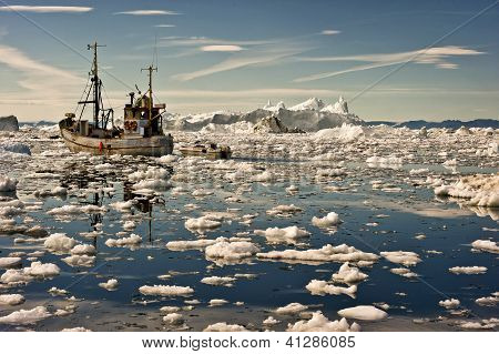Fishing boat going through the icy waters at dawn of Ilulissat, Greenland