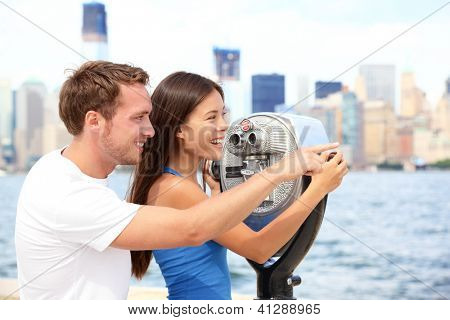 Tourists couple travel in New York. Beautiful young interracial young couple on travel looking at Manhattan and New York City skyline from Ellis Island. Asian woman, Caucasian man.