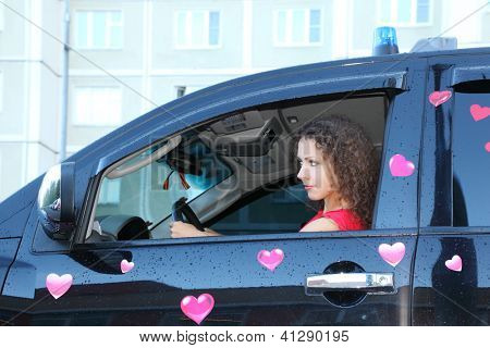 Young beautiful woman at wheel of black wet  offroader with stickers hearts. Pink wedding.