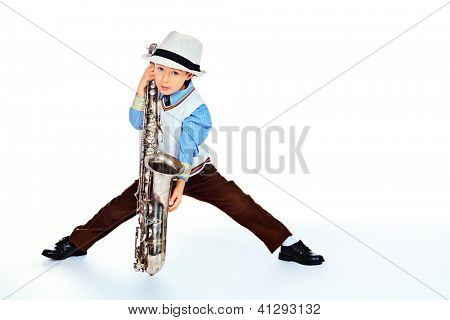 Portrait of a cute little boy jazzman playing his saxophone. Isolated over white.
