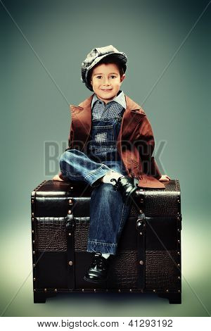 Portrait of a cute little boy sitting with a huge old trunk. Vintage style.