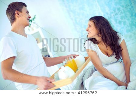 Happy female looking at her husband holding tray with breakfast in the morning