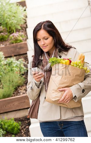Young woman holding bag groceries vegetables shopping smart phone texting
