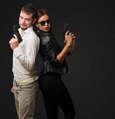 foto of hustler  - Young Couple Holding Gun against a black background - JPG
