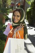 stock photo of dupatta  - Portrait of beautiful Indian woman smiling while holding shopping bags - JPG
