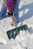 stock photo of snow shovel  - Person removing snow off path with shovel - JPG