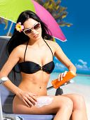 image of sun tan lotion  - Beautiful young woman in black bikini applying sun block cream on the tanned body - JPG