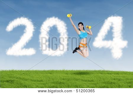 Fitness Young Woman Jumping With New Year 2014