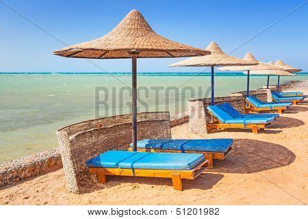Relájese bajo la sombrilla en la playa del mar rojo, Egipto