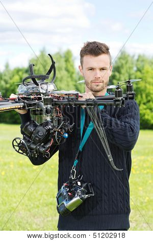 Portrait of confident male engineer holding UAV helicopter in park