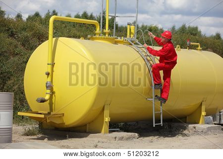 technician in red uniform climbing on large fuel tank