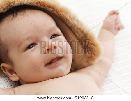 Closeup photo of adorable newborn baby smiling.