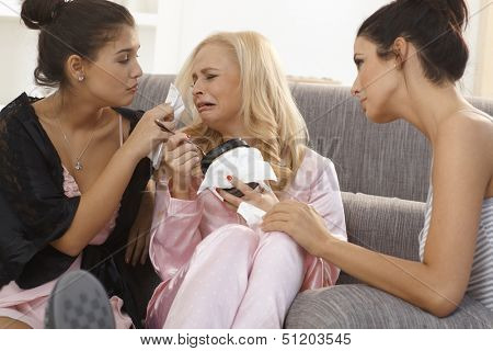 Female friends comforting crying girl at home, wearing pyjamas, wiping tears.