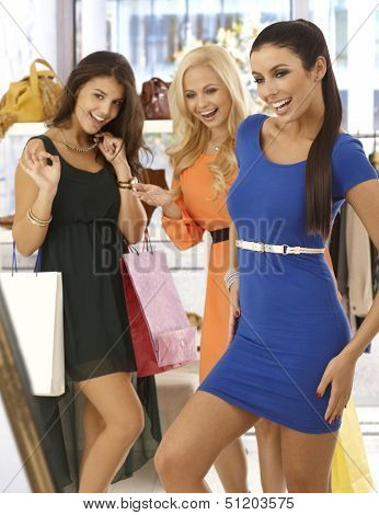 Happy girls shopping together, one trying on blue mini dress, friends looking at her with joy.