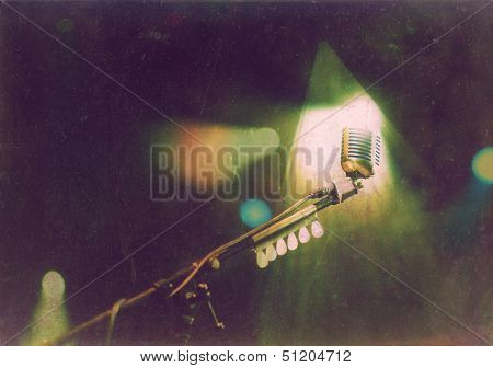 Vintage photo of retro styled microphone in stage lights during concert