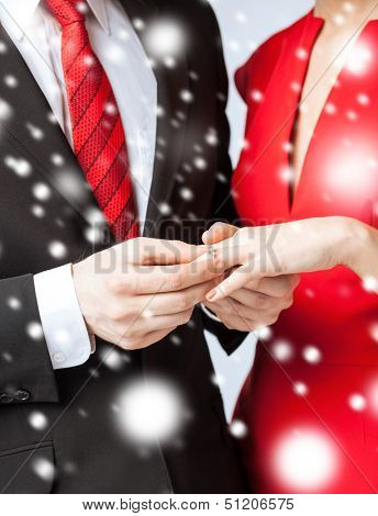 love, romance, marriage, jewelry concept - man putting wedding ring on woman hand