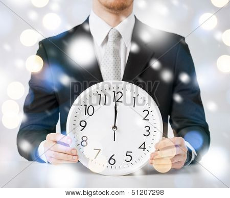 holiday, celebration, new year's eve concept - man holding wall clock showing 12