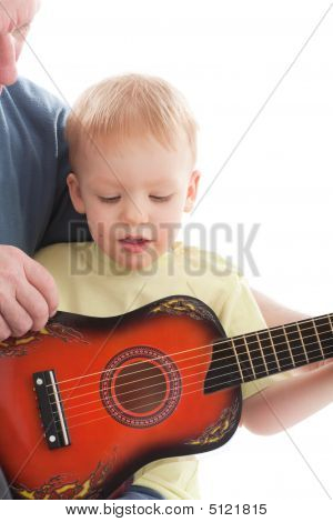 Grandfather Teaching Grandson Play On Acoustic Guitar