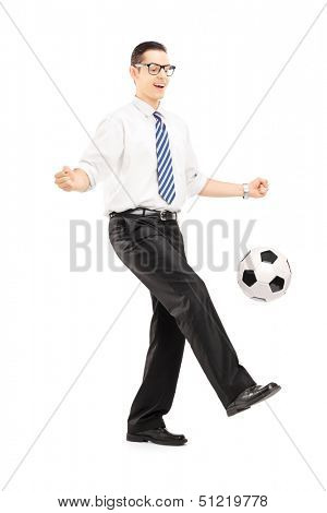Full length portrait of a handsome male with tie and shirt playing with a soccer ball, isolated on white background