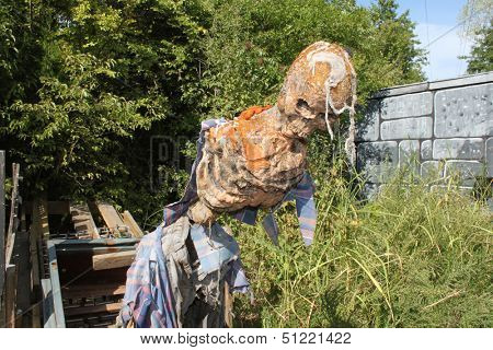 Decomposed skeleton with pieces of clothes stands in the middle of the overgrown yard.