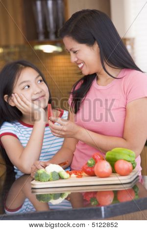 Mother Offering Daughter A Piece Of Freshly Chopped Pepper