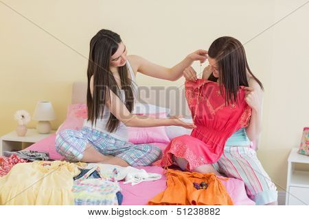 Girls looking at dresses at a sleepover in bedroom at home