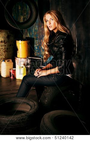 Stunning blonde woman in black leather jacket and pants standing in the old garage.