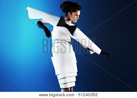 Art fashion photo of a gorgeous woman in paper dress over blue background. Black and white.