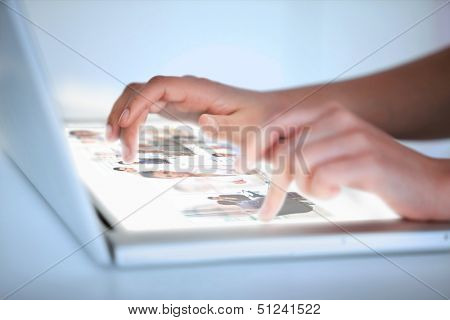 Close up of hands selecting pictures on a futuristic laptop on dark background