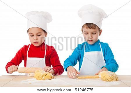 Two kids kneading the dough together