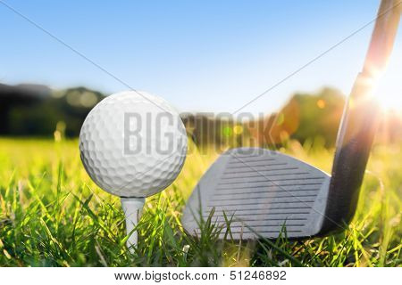 Golf ball on white tee and golf club preparing to shot. Green grass golf course. Blue sunny sky
