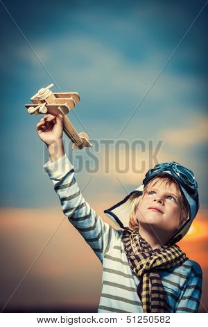Little boy with wooden plane