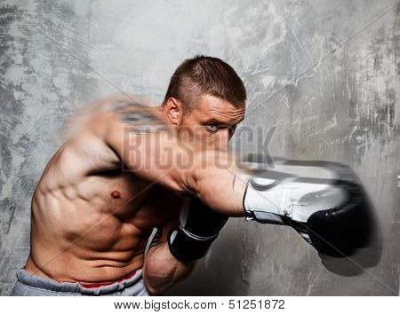 Young man in boxing gloves making punch