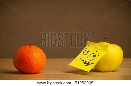 Apple with sticky post-it note reacting at orange