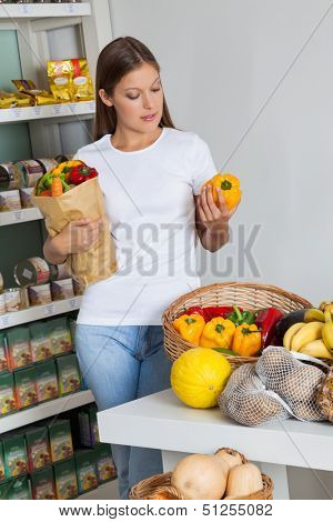 Young woman shopping bellpeppers in supermarket