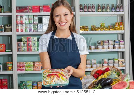 Portrait of beautiful young woman holding vegetable packet in supermarket
