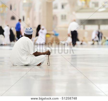 Muslim man sitting on ground and praying