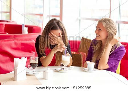 Two beautiful and elegant woman sitting in cafe/Friends drink coffee