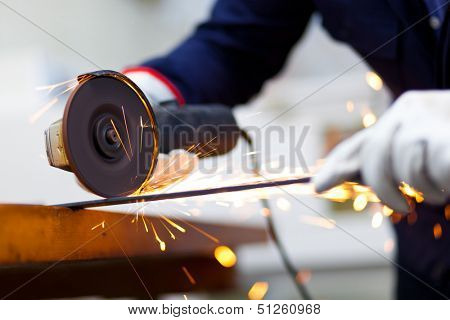 Worker grinding a metal bar
