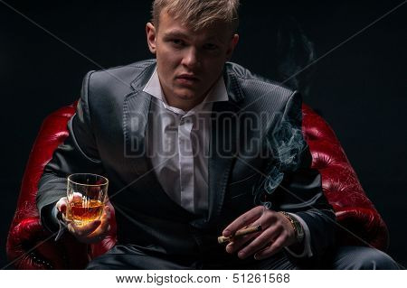 Mafia Boss In The Red Chair. Dramatic Lighting