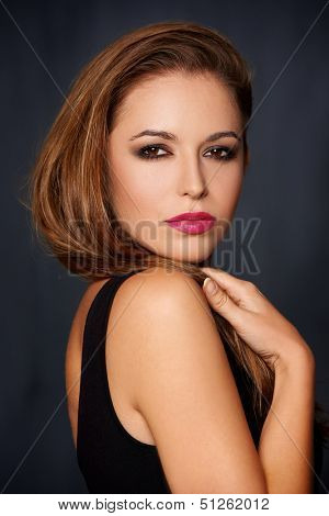 Sexy seductive woman with long brunette hair and red lipstick looking sideways at the camera with a sultry look over a dark studio background