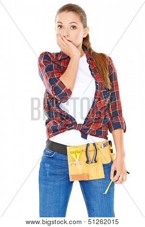 Capable young woman dressed in jeans with a tool belt around her waist standing looking at the camera with a worried look and her hand to her chin  isolated on white