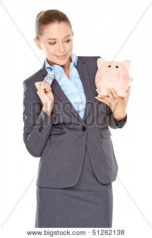 Woman deciding whether to spend or save holding a dollar bill in one hand and her piggy bank in the other with a wry expression  isolated on white
