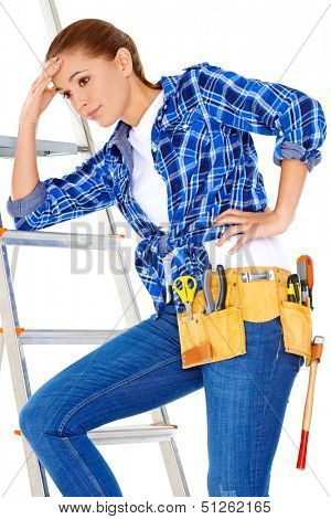 Young DIY handy woman with a problem standing on her stepladder with her head on her hand staring thoughtfully at the ground  isolated on white