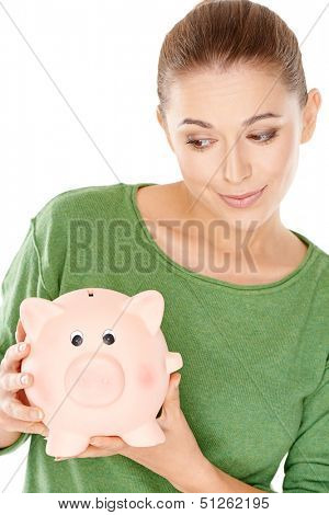 Beautiful young woman giving her large pink piggy bank a speculative look as she holds it in her hands